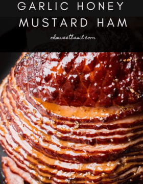 A close up of a spiral glazed honey mustard ham on a black platter with a basting brush
