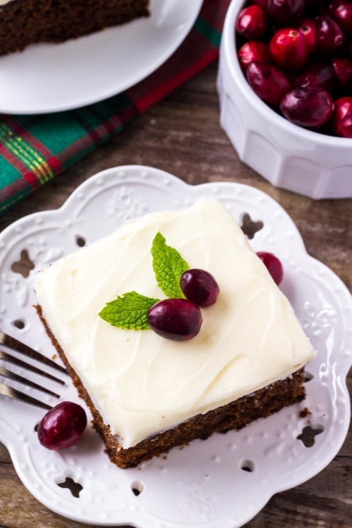 slice of Gingerbread Cake with Cream Cheese Frosting topped with fresh cranberries and mint leaves
