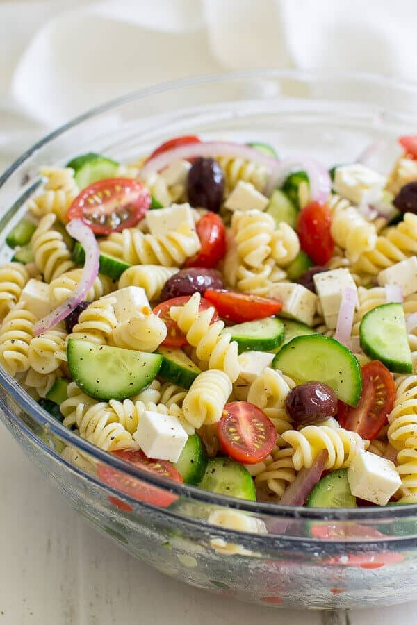 Greek Pasta Salad in a clear bowl on a white wooden table.