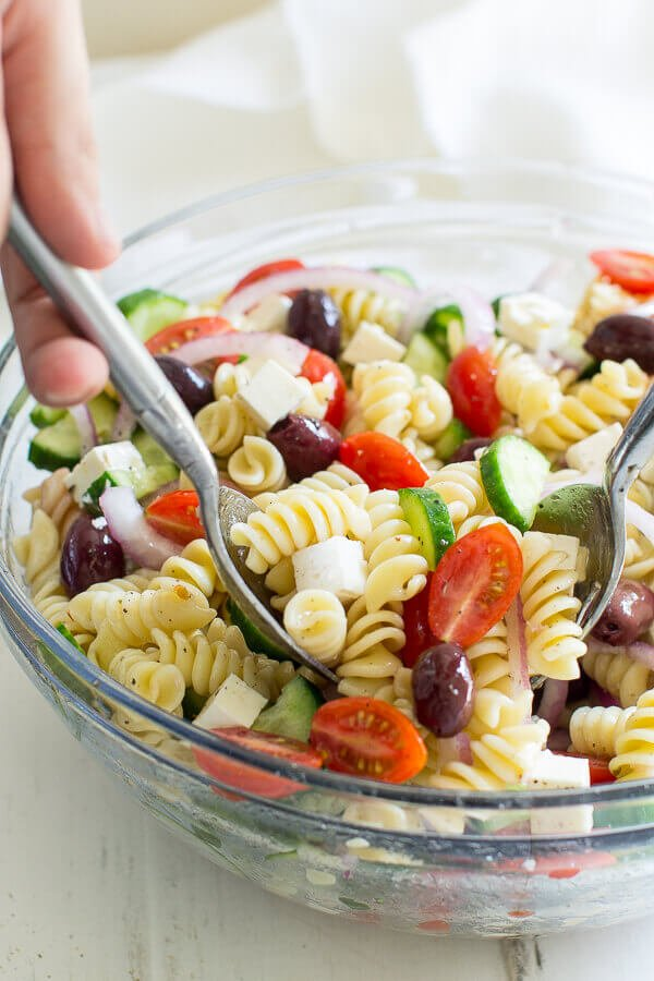 Grabbing two scoopfuls of Greek Pasta Salad in a clear bowl.