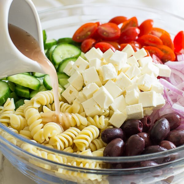 Pouring red wine vinaigrette into a bowl full of Greek Pasta Salad ingredients.