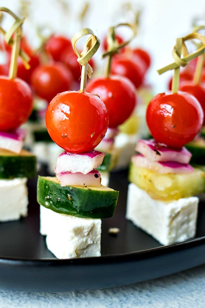 Greek Salad Skewers - Cherry tomatoes, cucumber, and red onion are tossed in a homemade Greek vinaigrette and layered on mini skewers with a little square of feta cheese.