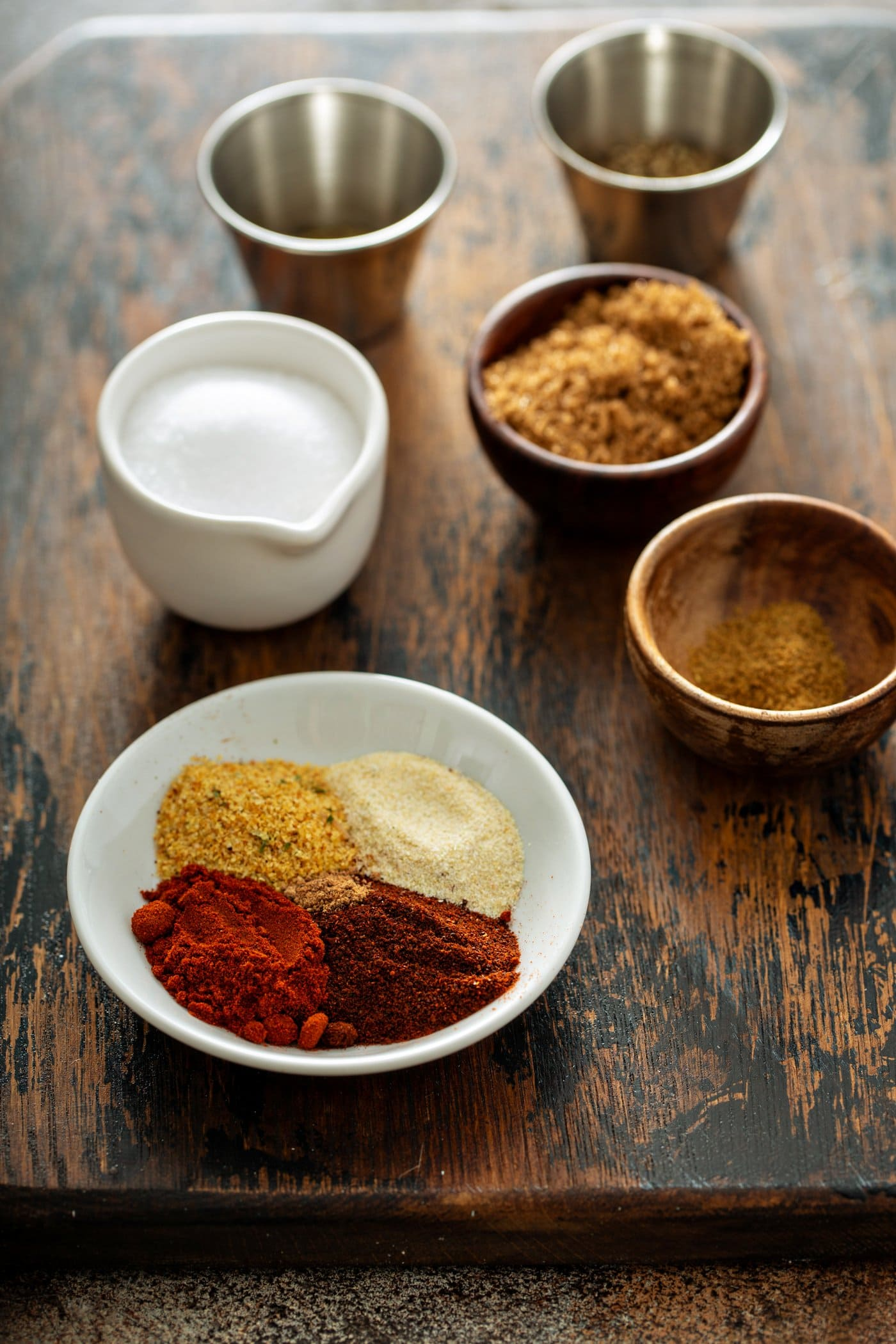 Ingredients for the rub for grilled bbq ribs. little containers of paprika, onion powder, garlic powder, and cumin. a container of salt, a little bowl of brown sugar, thyme and nutmeg.