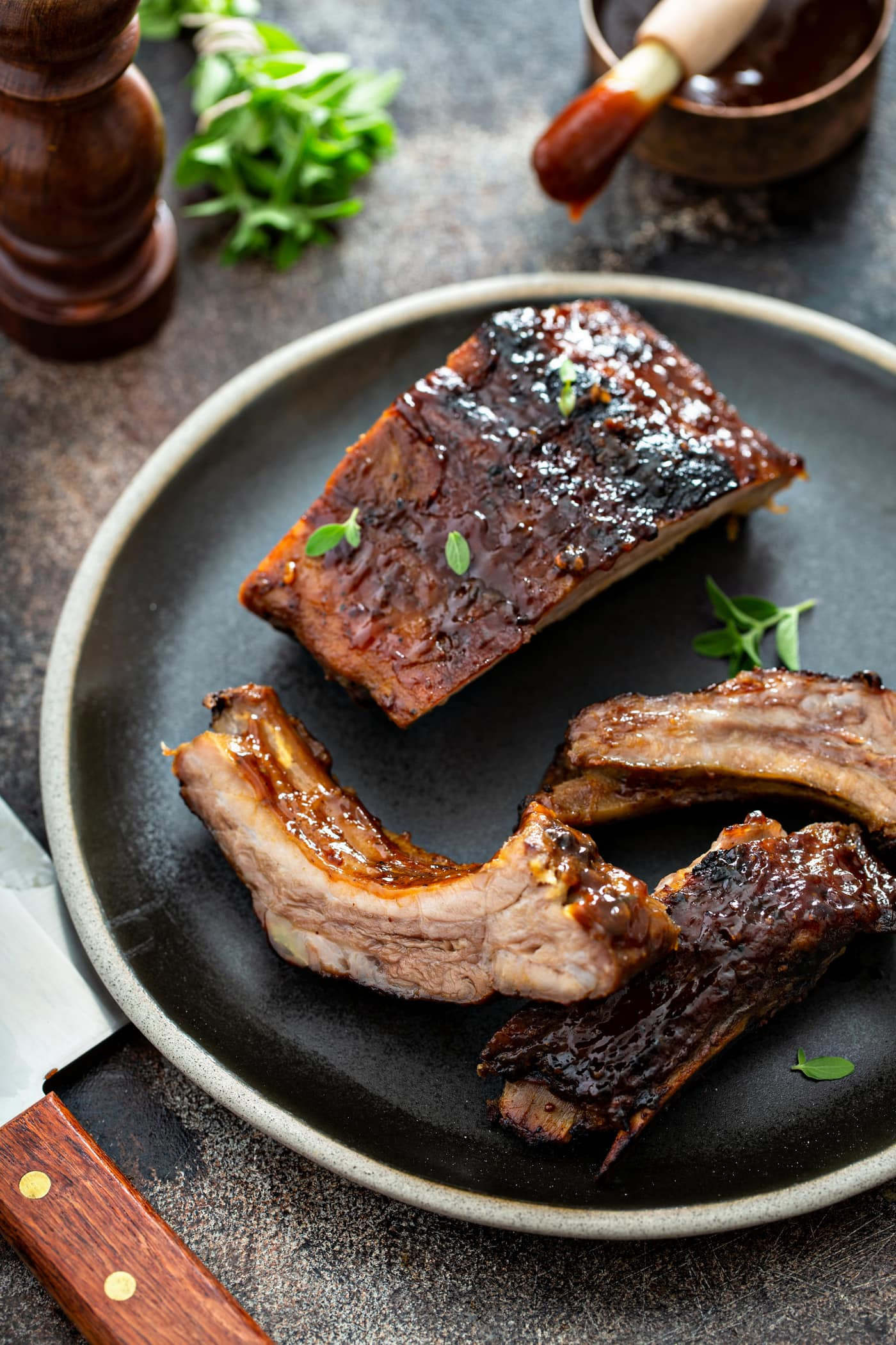 Three grilled pork ribs on a dinner plate.