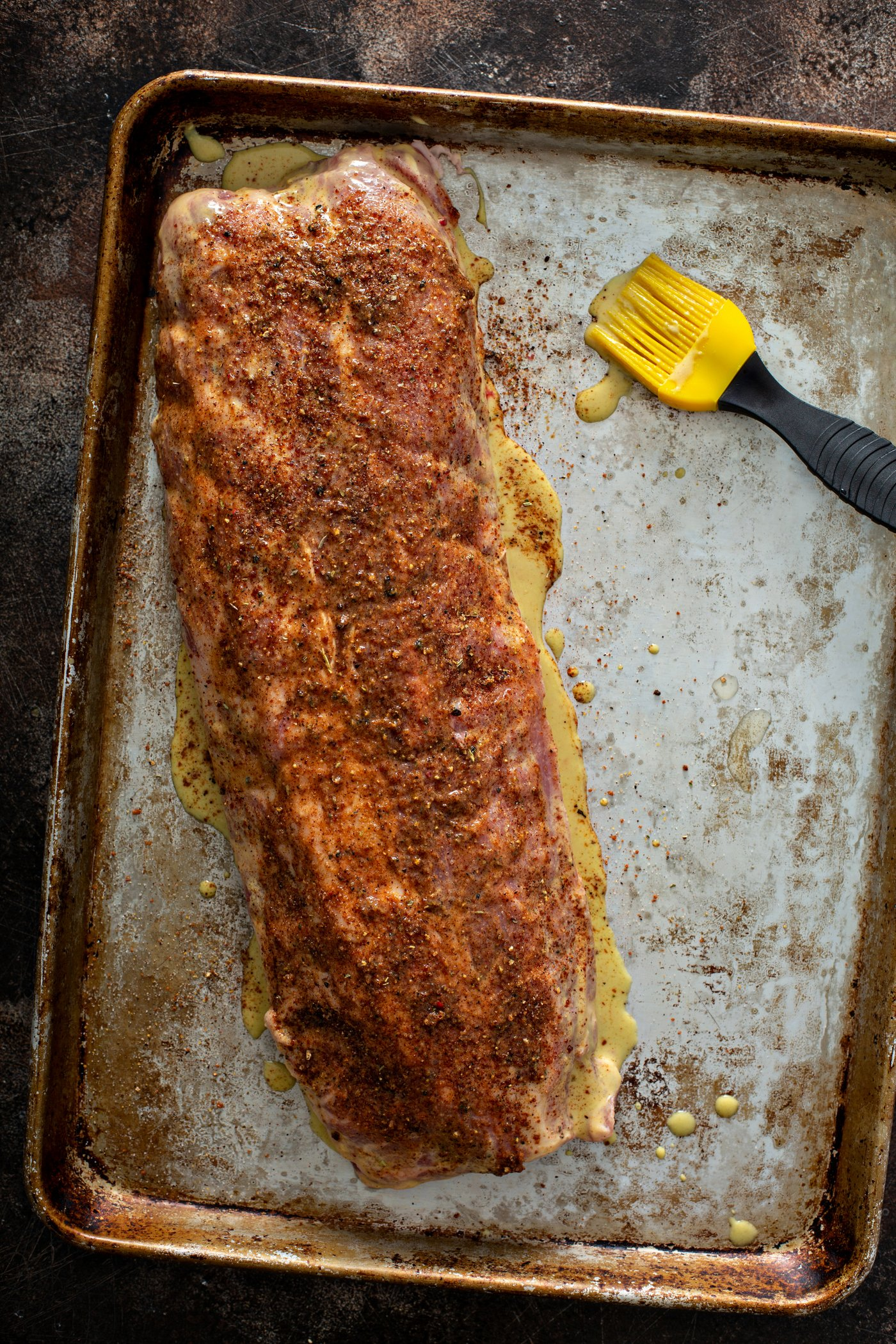 A rack of ribs covered with bbq rub and ready to go on the grill.