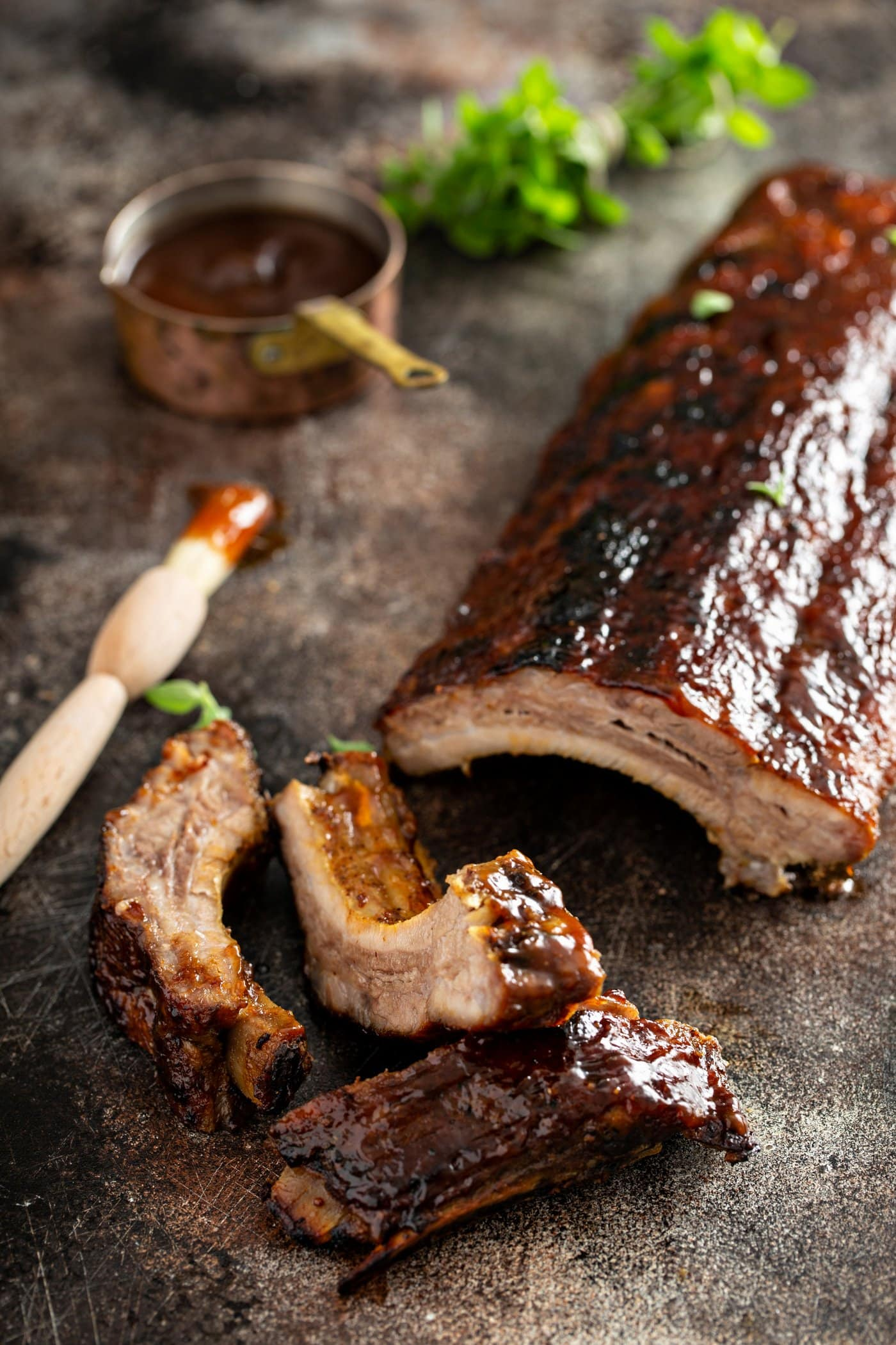 A rack of grilled pork ribs with a couple of ribs that are sliced off. A brush with glaze and a measuring cup of rub are in the background.