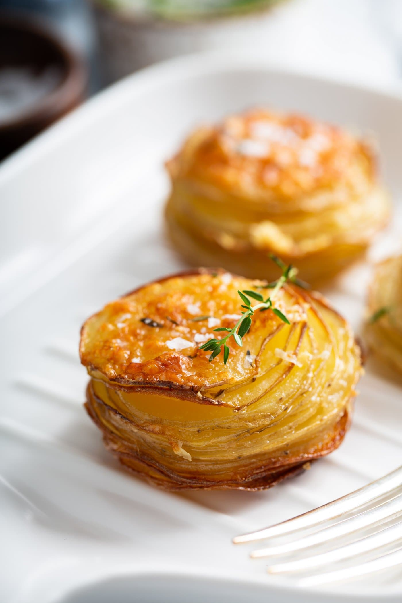 Two stacks of gruyere potatoes. They are shaped like muffins and they are baked to a golden brown.