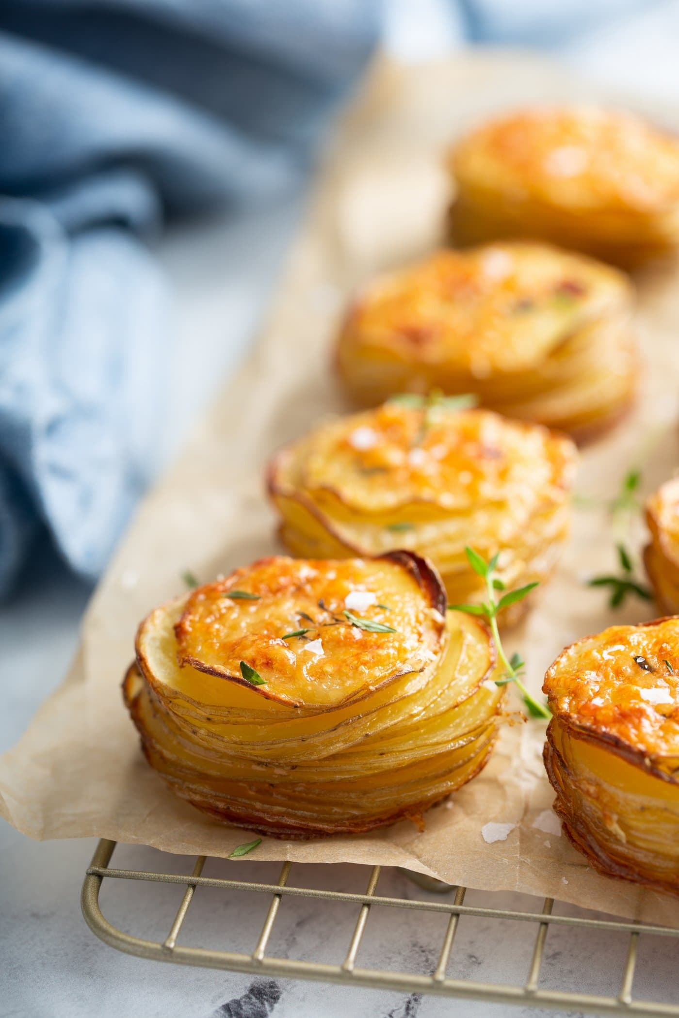 Slices of gruyere potatoes baked to a golden brown, sitting on a wooden cutting board.