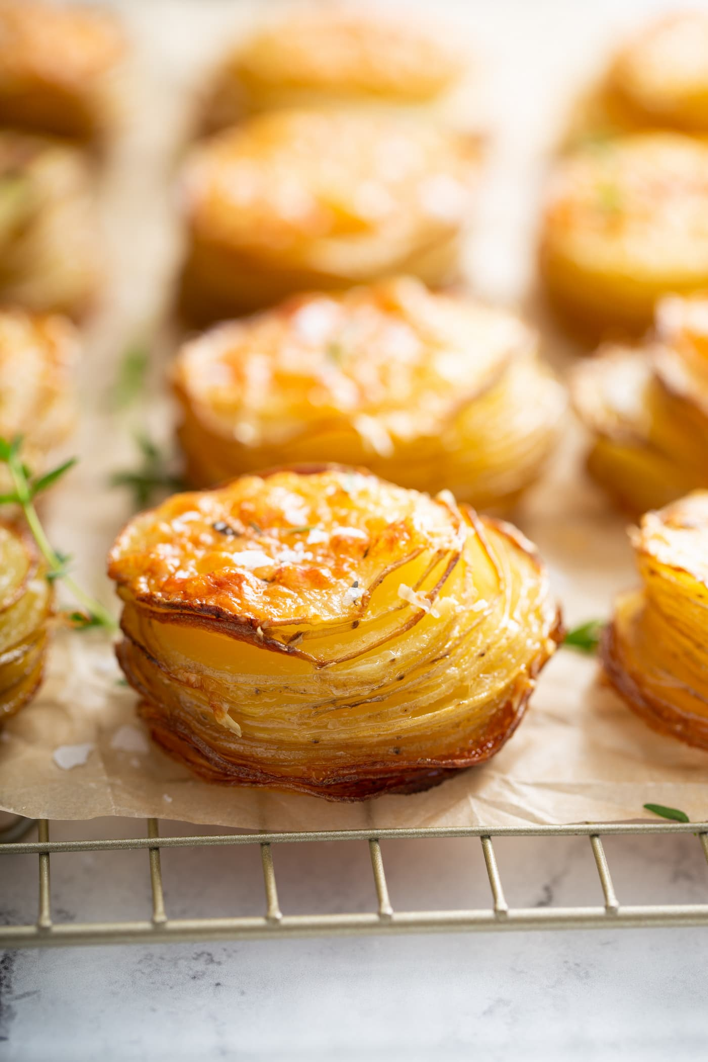 Gruyere potatoes baked to a golden brown sitting on a wooden cutting board.