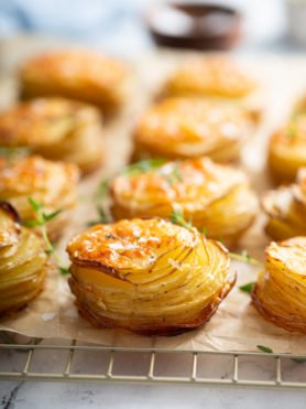 Gruyere potatoes that are baked to a golden brown sitting on parchment paper on a wire cooling rack.