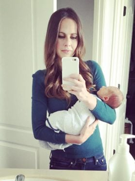 A photo of me in the mirror holding our new baby at home.