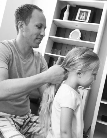 A photo of Cade braiding one of our daughter's hair.