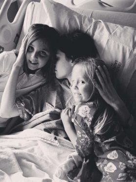 A photo of my in a hospital bed snuggling my two girls.