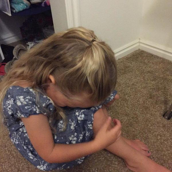 A photo of our daughter curled up on the floor crying.