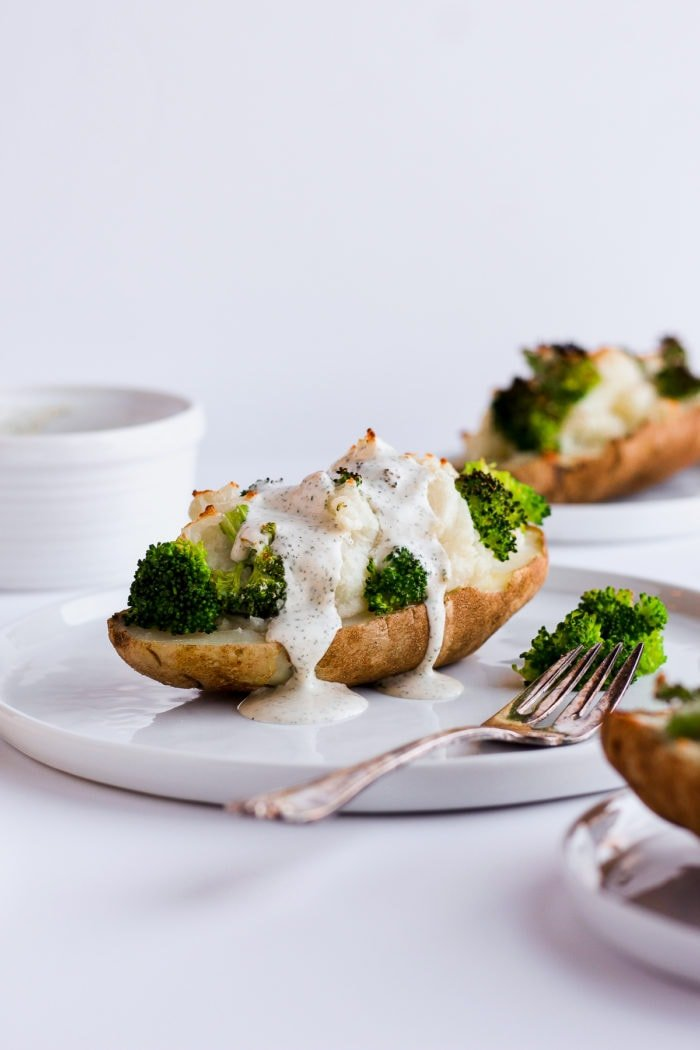 A white plate with half a potato stuffed with mashed potatoes with broccoli and sauce dripping down the sides