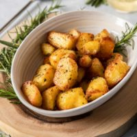 A cream coloured bowl filled with herby roasted potatoes, surrounded by fresh herbs. It sits on a wooden board