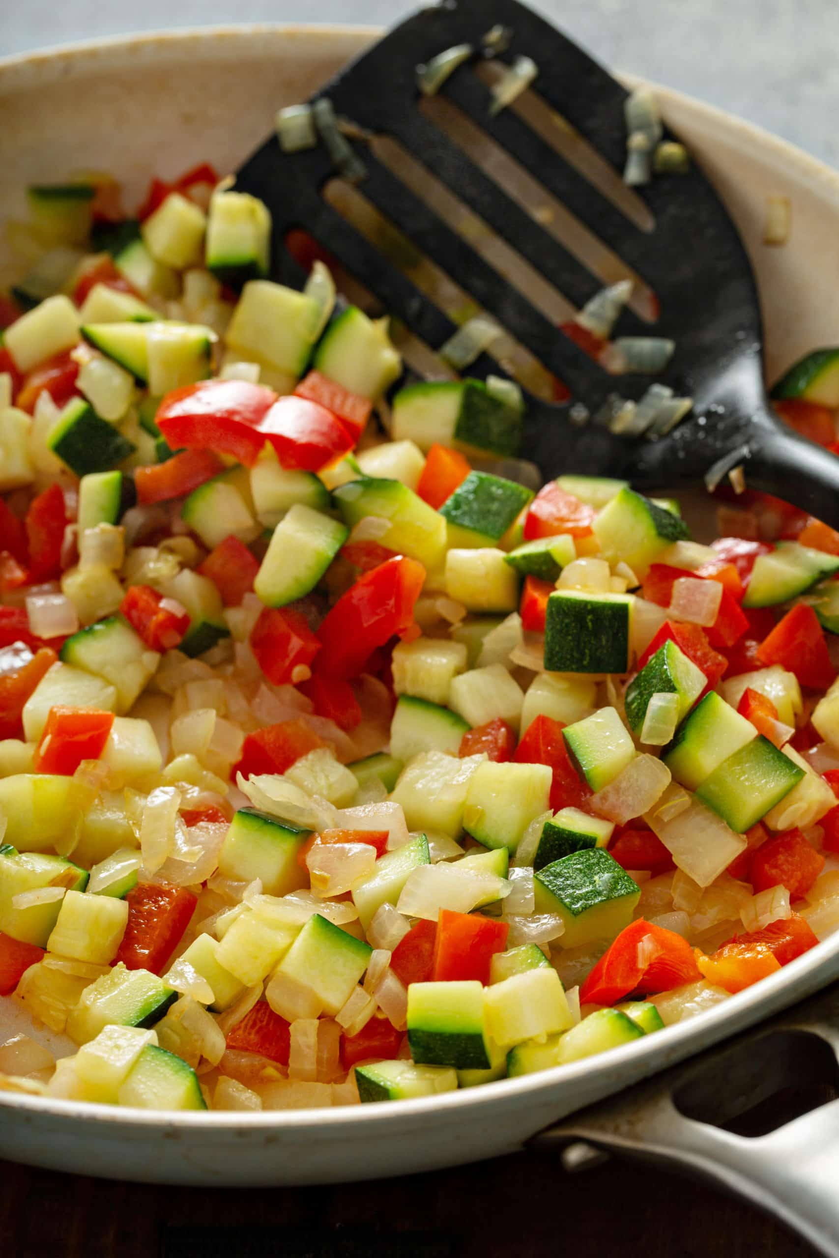 Chopped red bell pepper, zucchini, and onions.