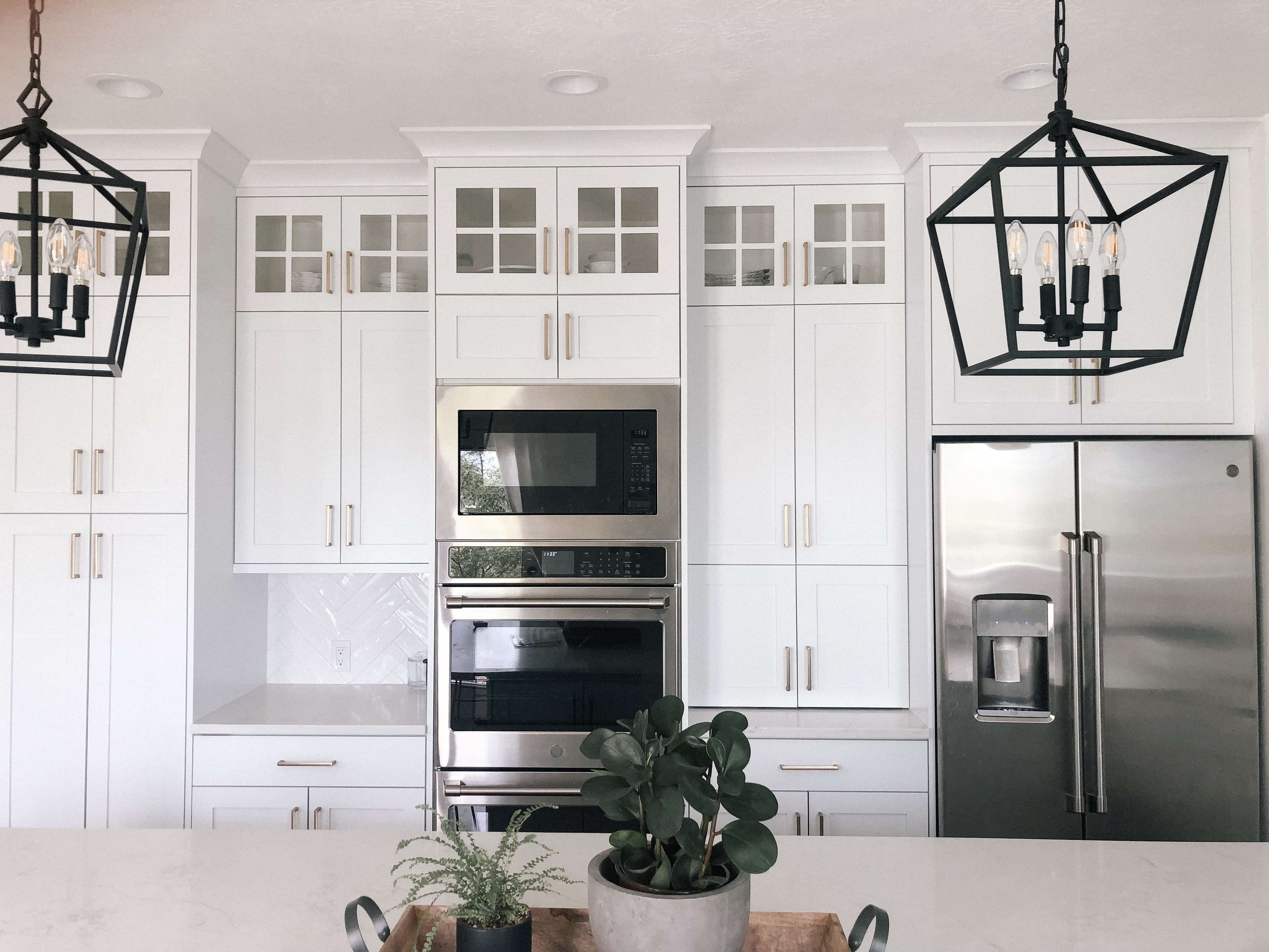 an all white kitchen with long island. White counter tops and white cabinets with glass windows on top and black lantern lights. full pantry door with glass windows as well and natural wood floating shelves!