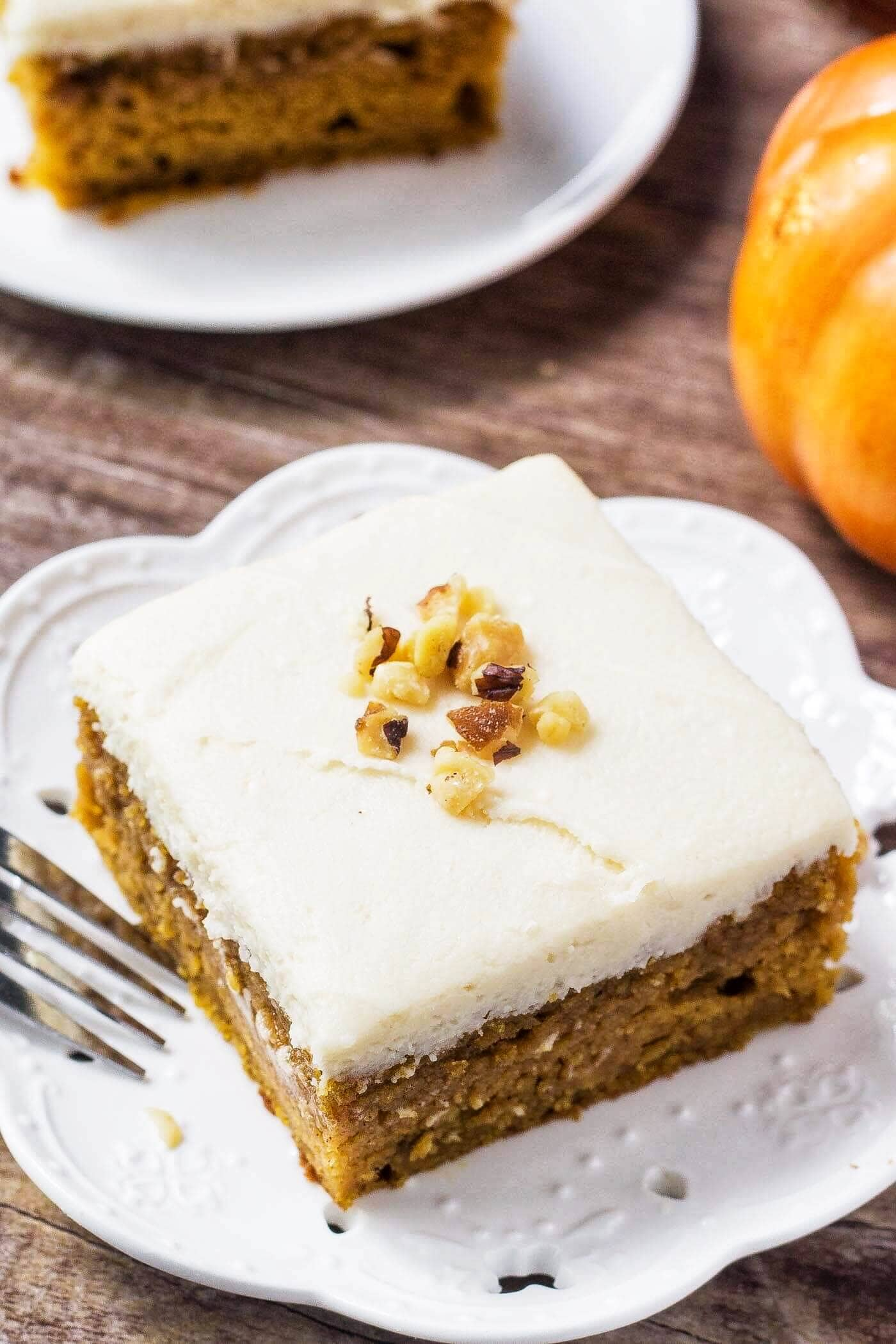 slice of pumpkin cake with maple frosting on white plate