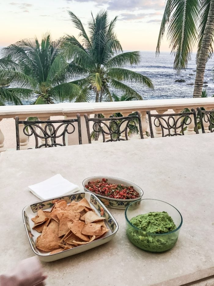 homemade chips, guacamole and salsa on a patio with palm trees and the beach and sea of cortez behind it