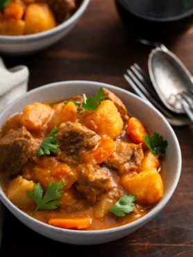 A bowl of instant pot beef stew. There are chunks of beef, carrots and potatoes with fresh parsley leaves sprinkled on top. A fork and spoon are next to the bowl.