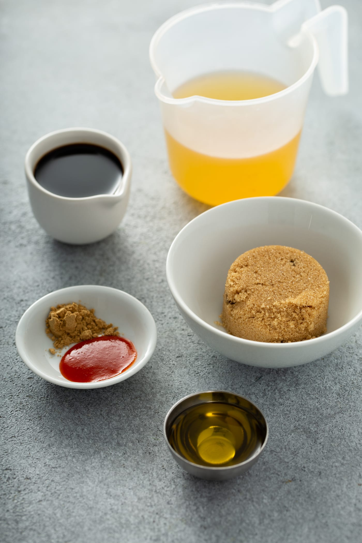 A photo of all the ingredients in separate dishes to make the sauce for beef and broccoli, including beef broth, soy sauce, brown sugar, ground ginger, sriracha sauce, and sesame oil.