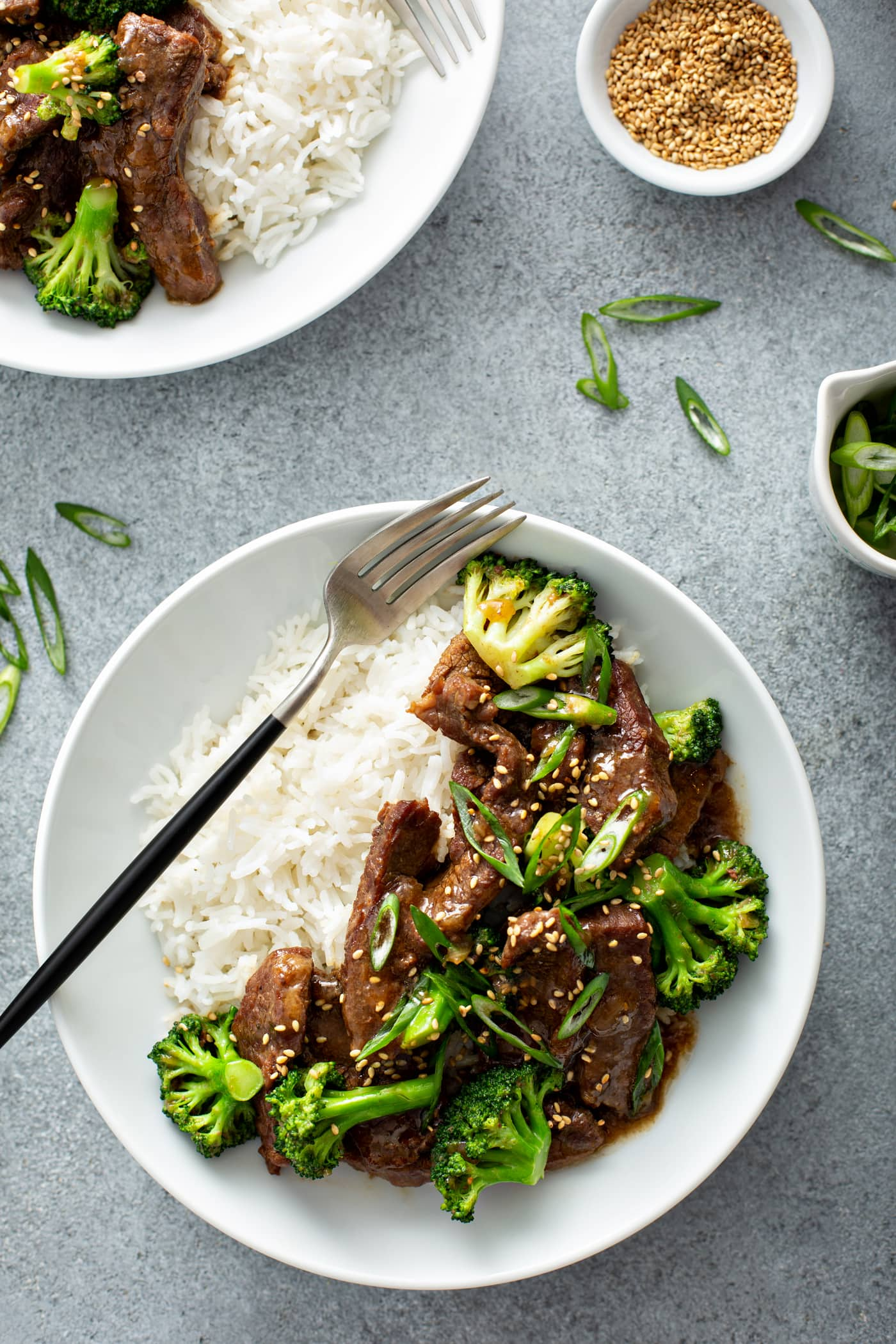 A photo of a white bowl full of beef and broccoli and a side of white rice with a fork sitting on top of ther rice.