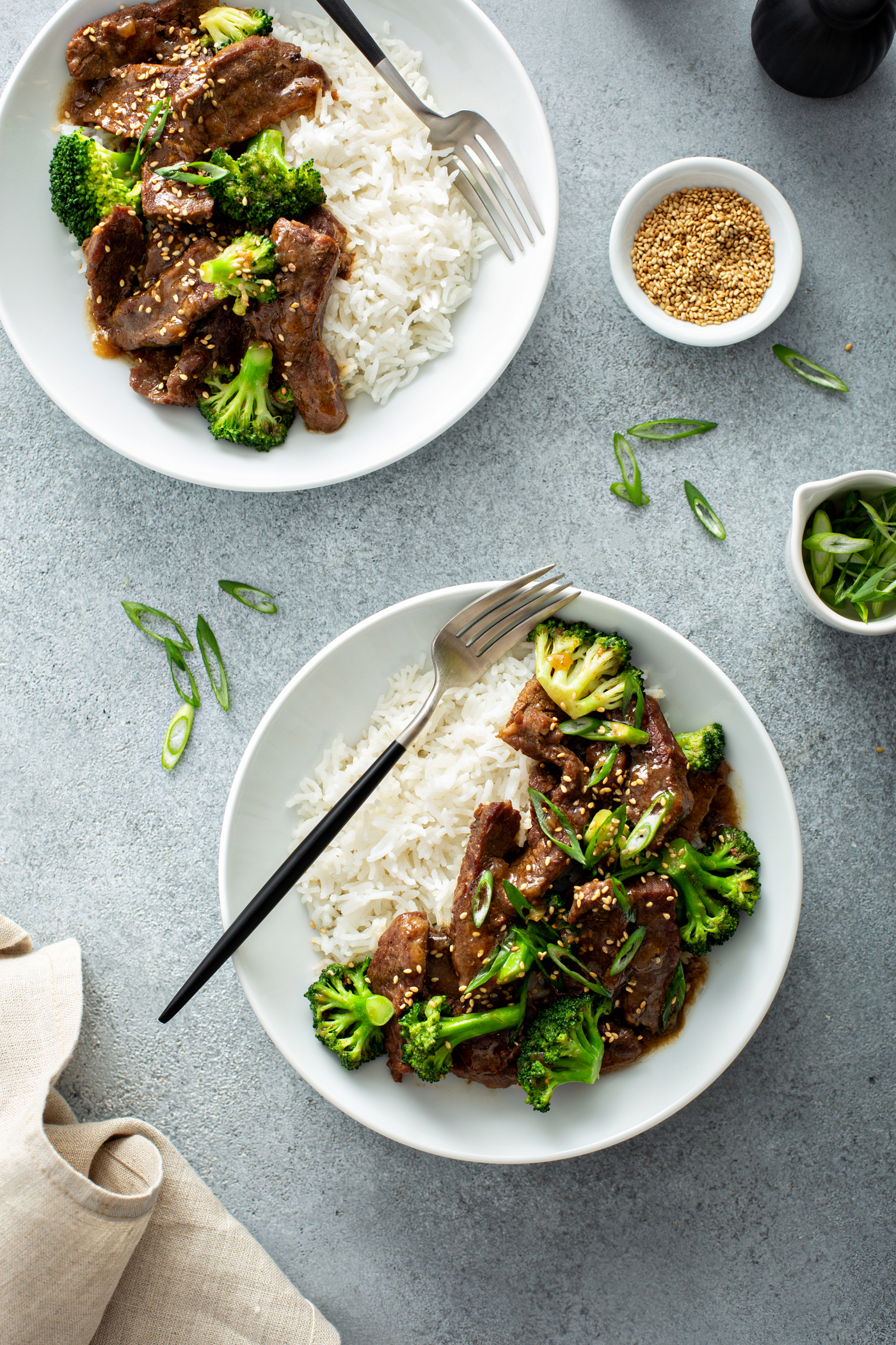 A photo of two bowls of beef and broccoli with a side of white rice.