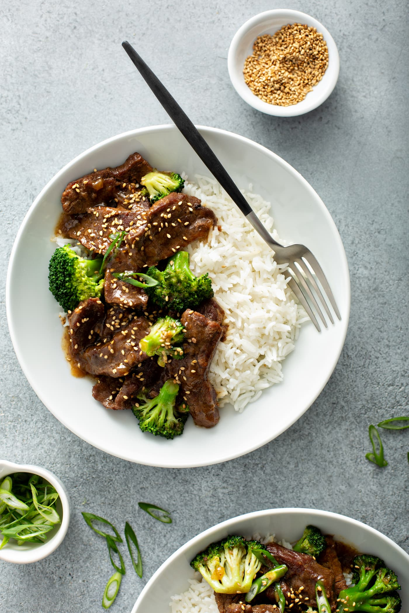 A photo of a white bowl with a serving of beef and broccoli in it along side some white rice. There is also a small dish of toasted sesame seeds next to the bowl.