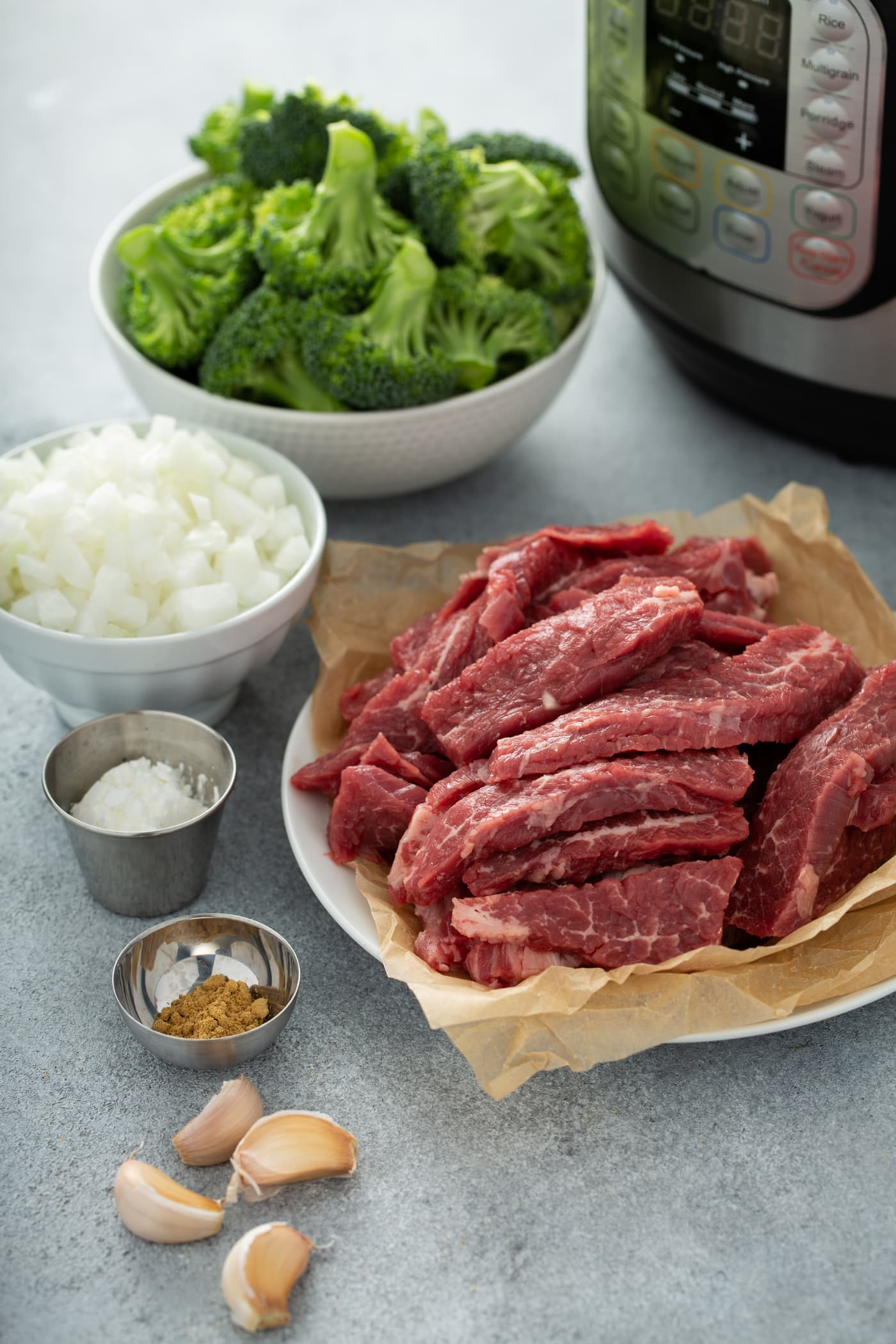 A photo of the ingredients needed to make beef and broccoli with an Instant Pot in the background. The ingredients are in separate bowls, including broccoli florets, chopped onion, sliced raw flank steak, cornstarch, ground ginger and garlic cloves.