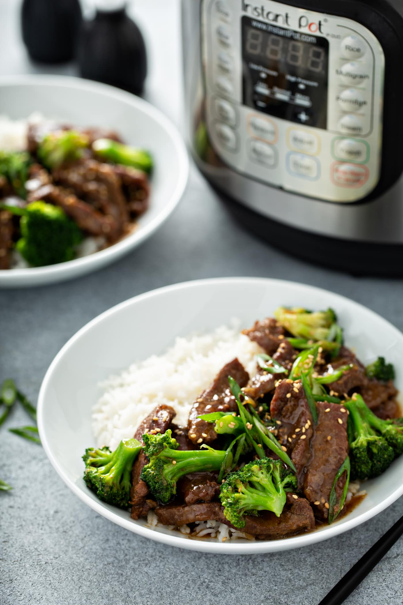 A photo of a white bowl full of beef and broccoli with a side of white rice.