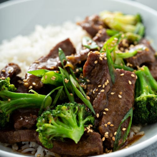 A close up of broccoli beef on a plate next to white rice.