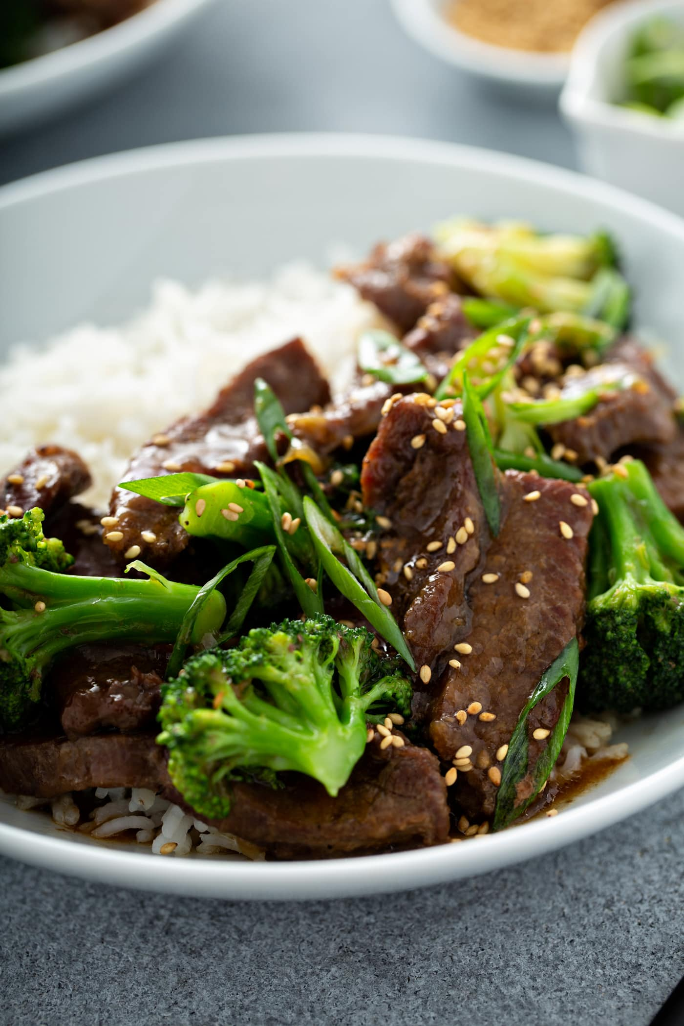 A photo of a white bowl of beef and broccoli garnished with toasted sesame seeds and green onions.
