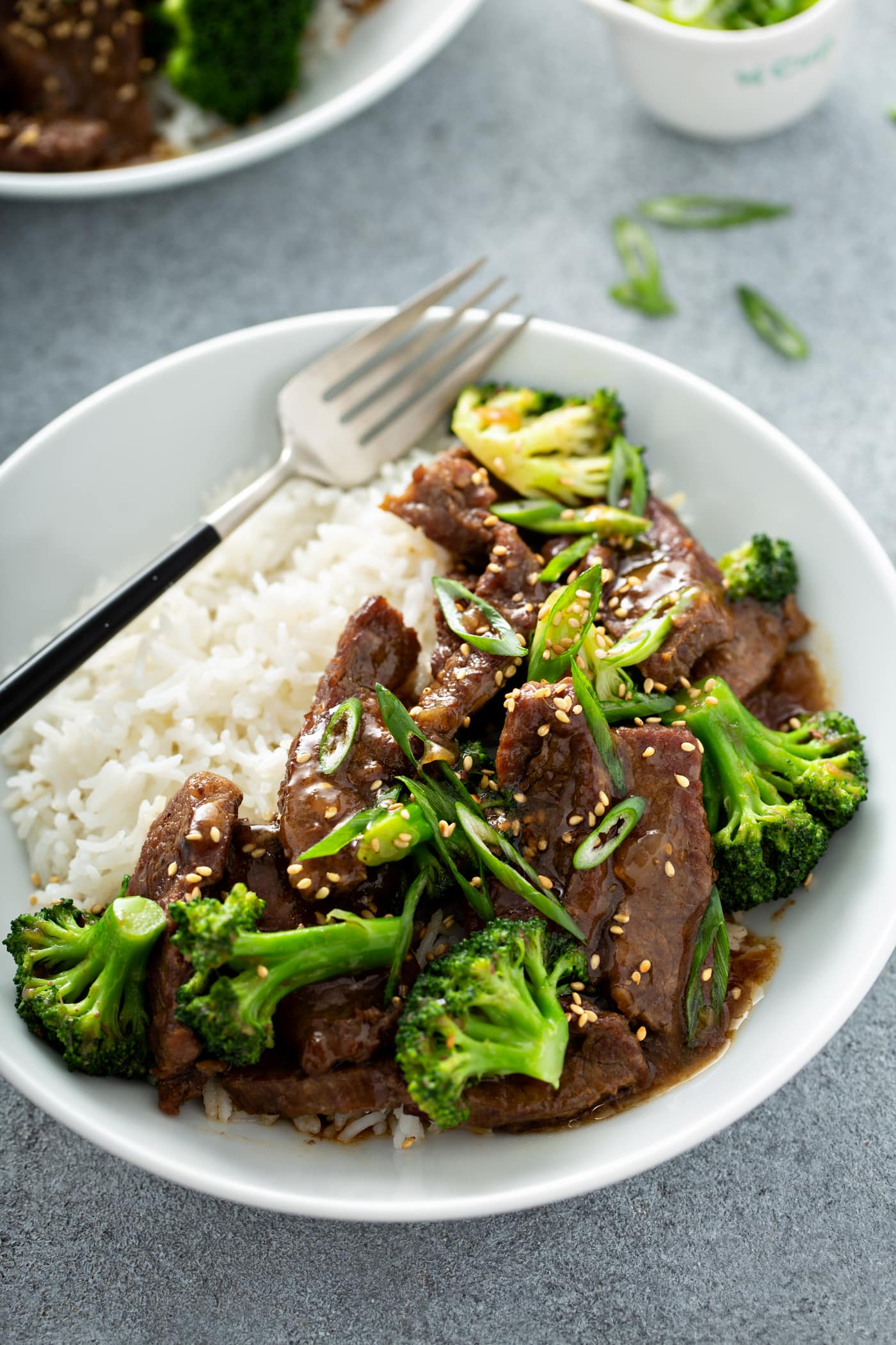 A photo of beef and broccoli on a white plate next to a serving of white rice and garnished with sliced green onions and toasted sesame seeds