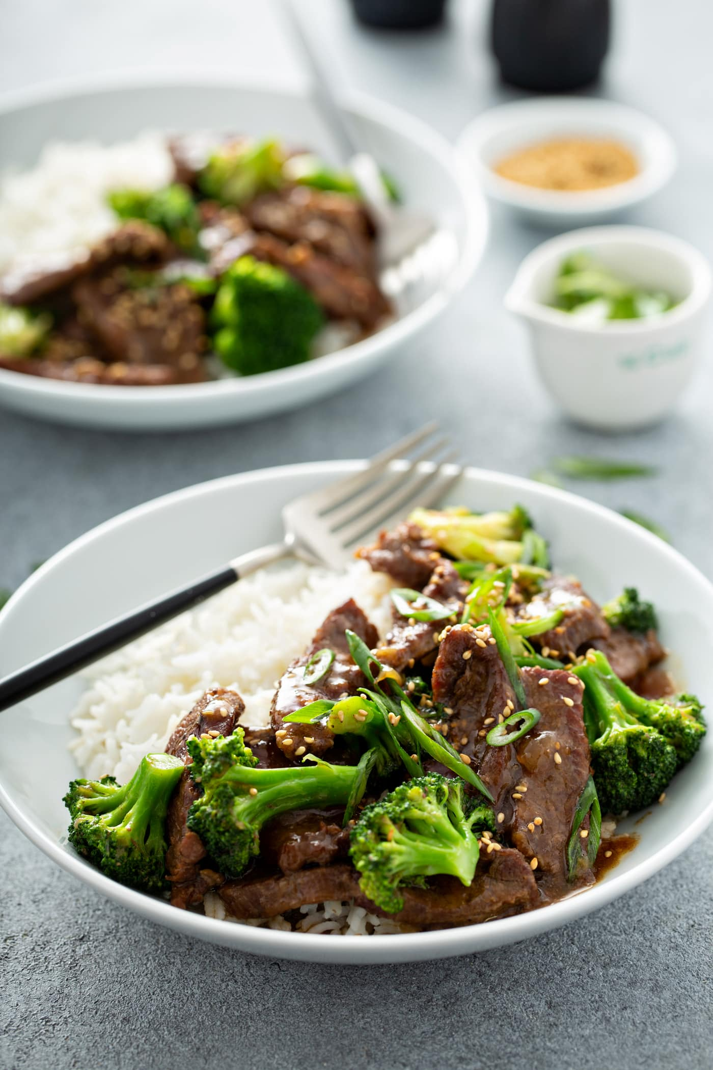 A photo of a bowl of beef and broccoli with another bowl of the same dish in the background.