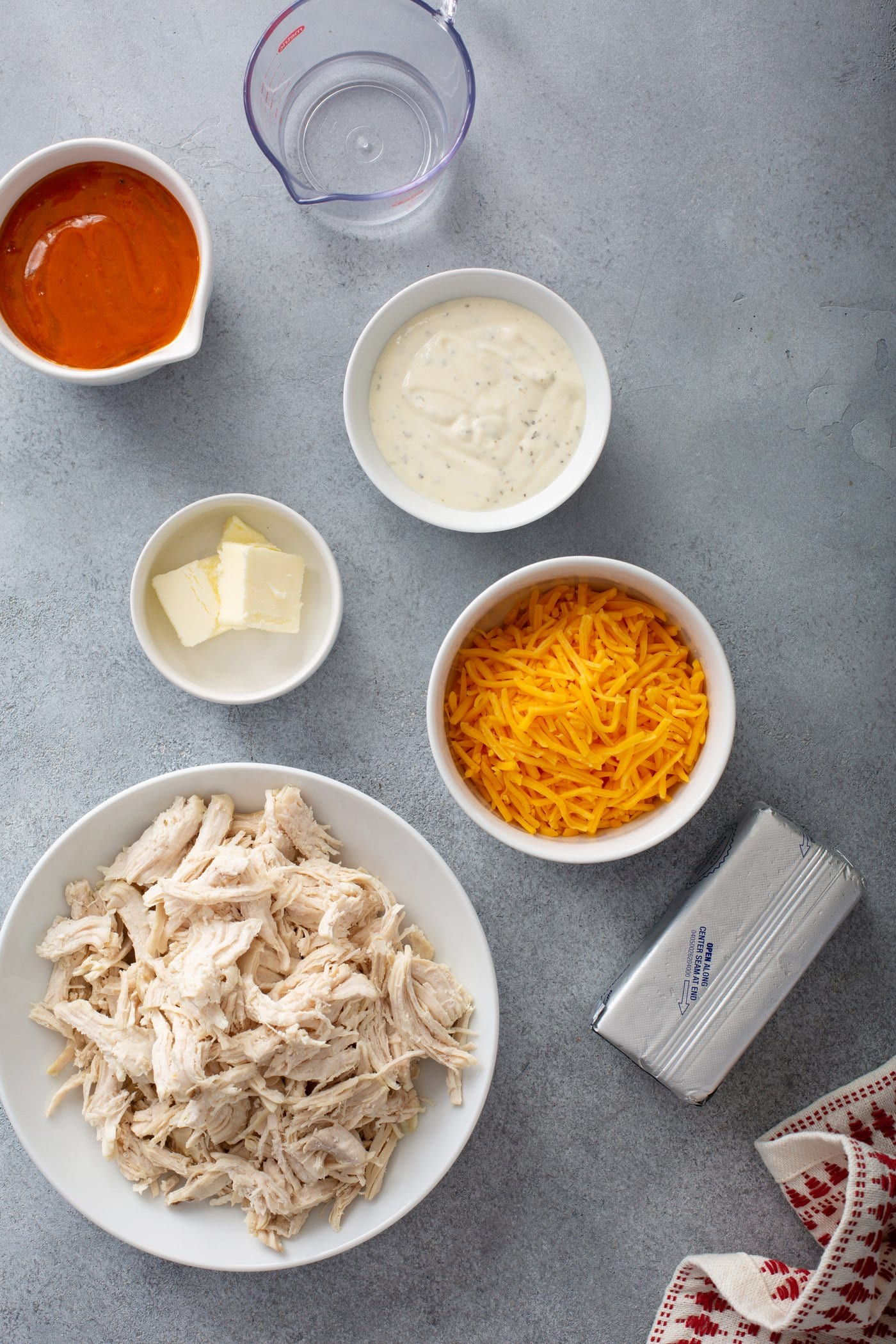 Small containers of shredded chicken, cheese, hot sauce, ranch dressing and butter.