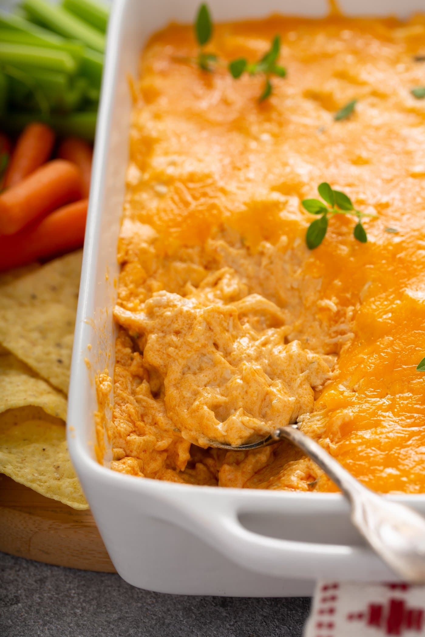 A casserole dish of buffalo chicken dip. A spoon is lifting a scoop of dip. There is shredded chicken in buffalo sauce with melted cheese on top. A few fresh parsley leaves are sprinkled on top. Chips and carrots are next to the dish of dip.