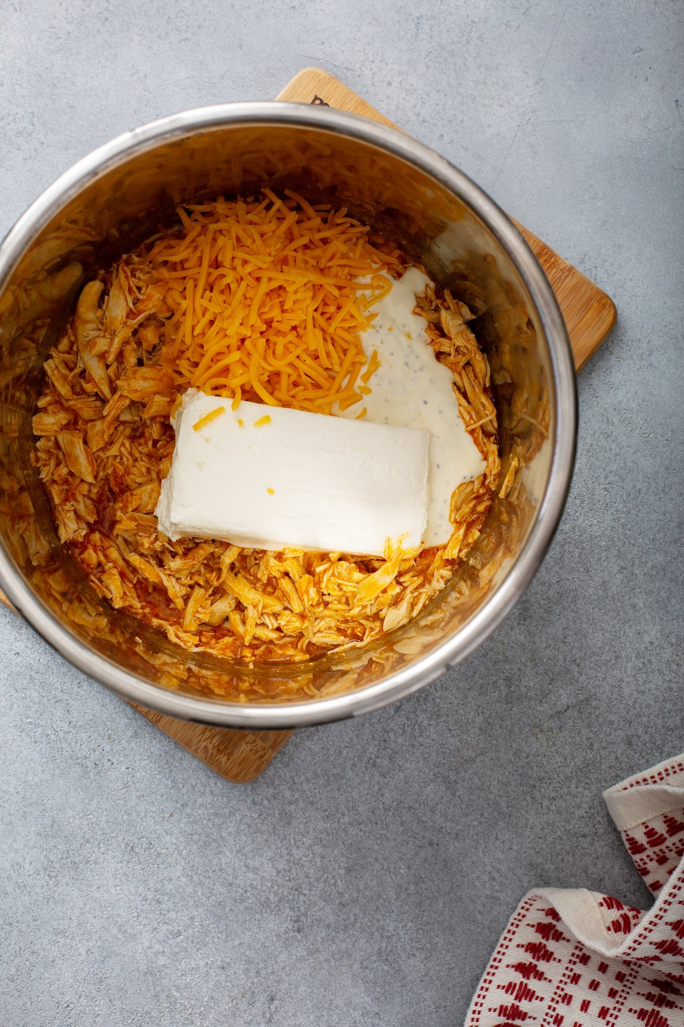 The pot of an instant pot with shredded chicken, cream cheese, shredded cheese and buffalo sauce.