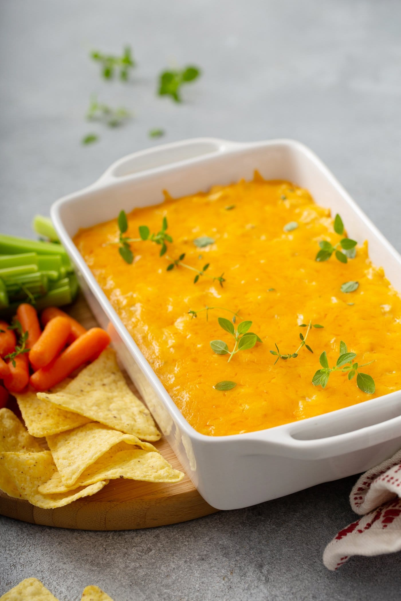A casserole dish filled with buffalo chicken dip. It is covered with melted cheese and sprinkles of parsley on top. There are chips, carrot sticks, and celery sticks next to the dish of dip.