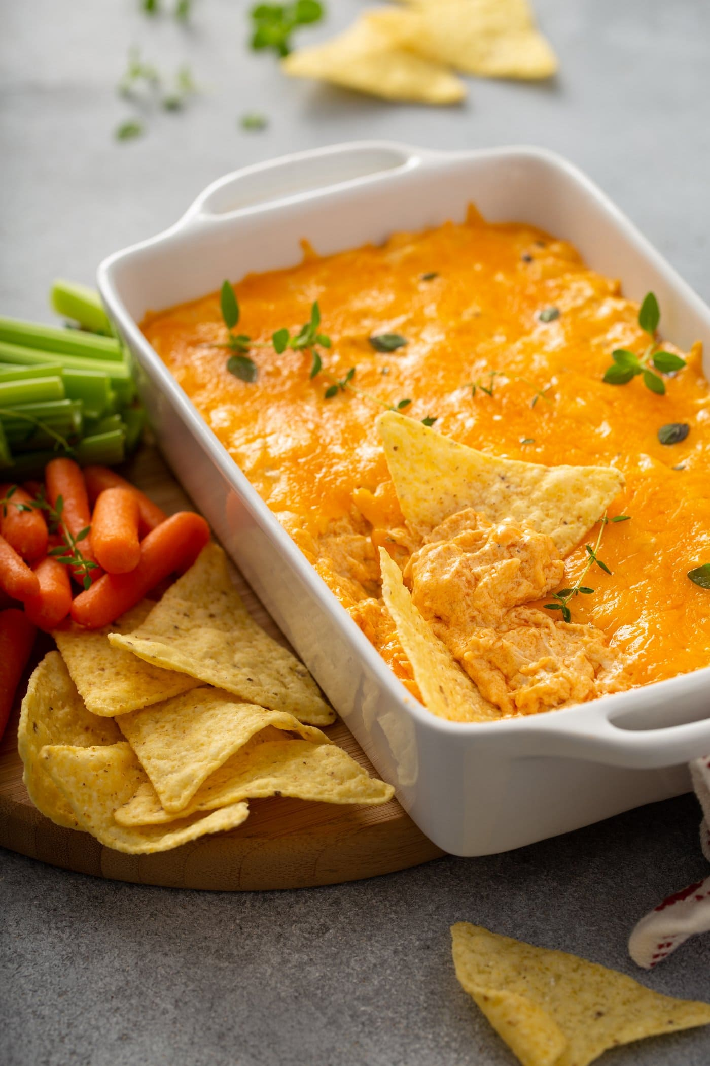 A casserole dish with buffalo chicken dip. A scoop has be taken out of the dip and there are a couple of chips laying in the dip. The dip is covered in melted cheese and sprinkled with parsley leaves. There are chips, carrots and celery laying next to the dip.
