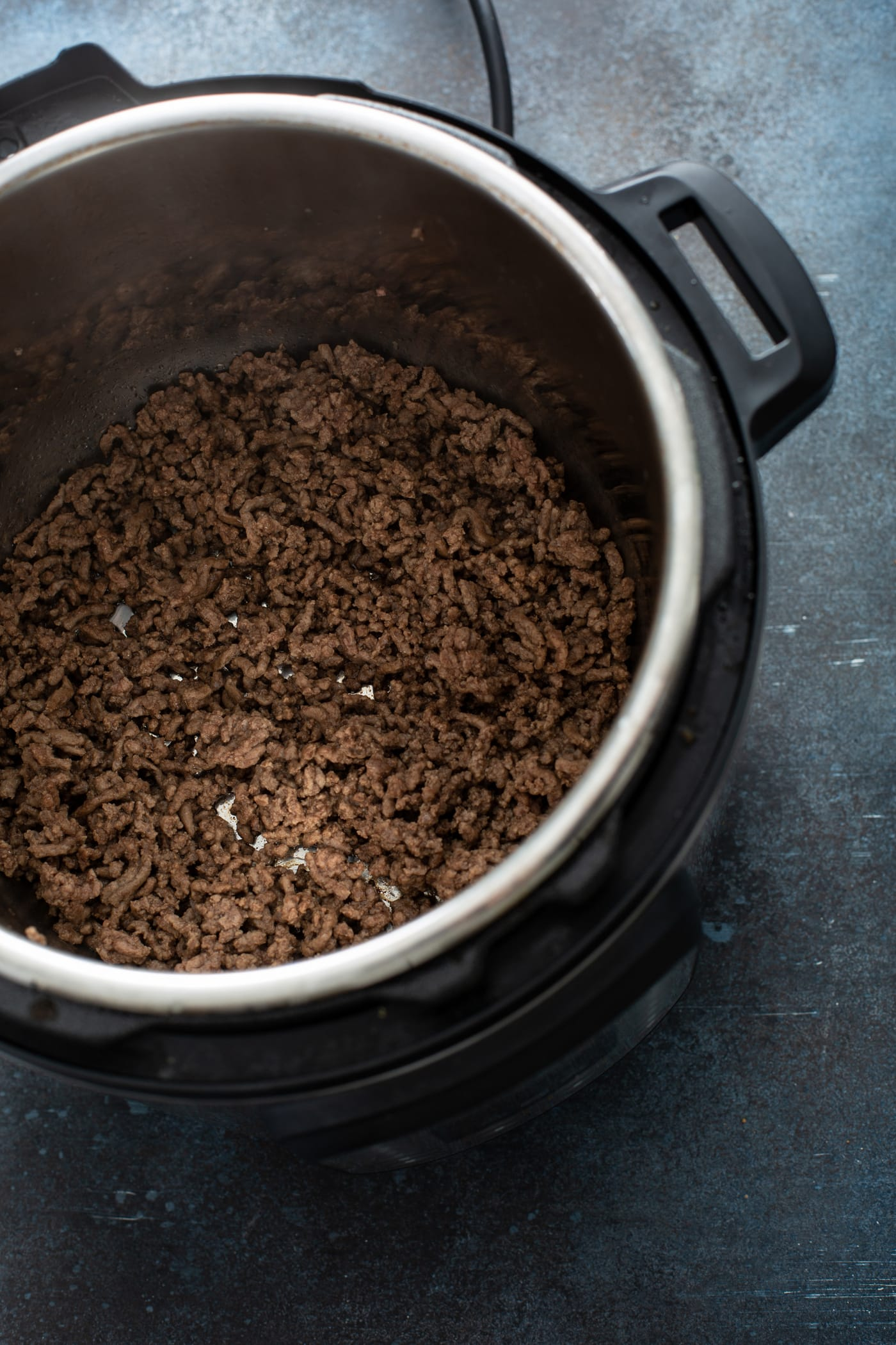An instant pot containing browned ground beef.