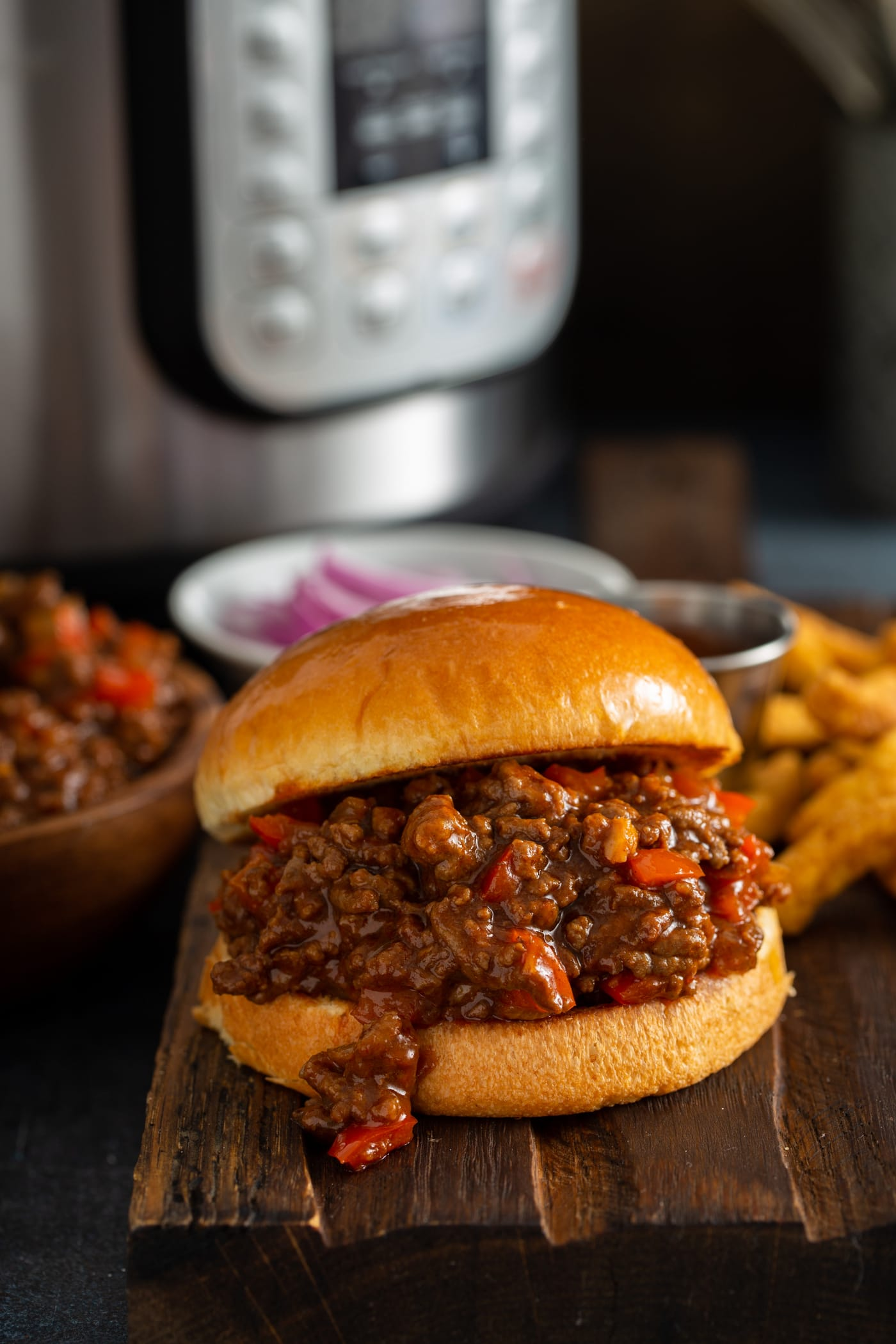 A toasted bun filled with sloppy joes filling. there is a bowl of sloppy joe, a bowl of sliced red onions, some french fries and an instant pot in the background.