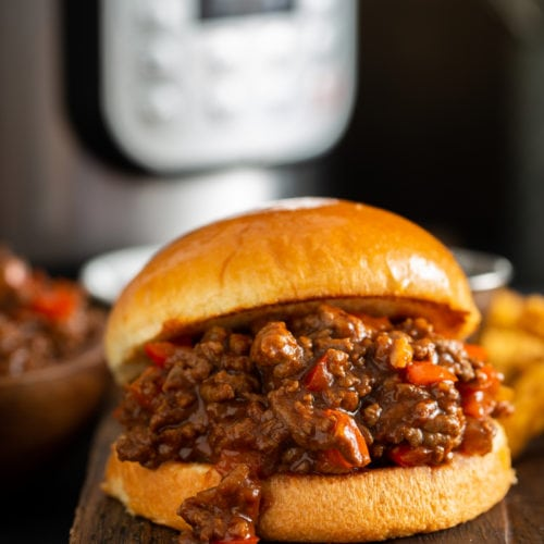 Sloppy joe on a toasted bun. The sloppy joe filling has browned ground beef and chopped red bell peppers in a thick sauce. There is an instant pot sitting behind the sloppy joe.