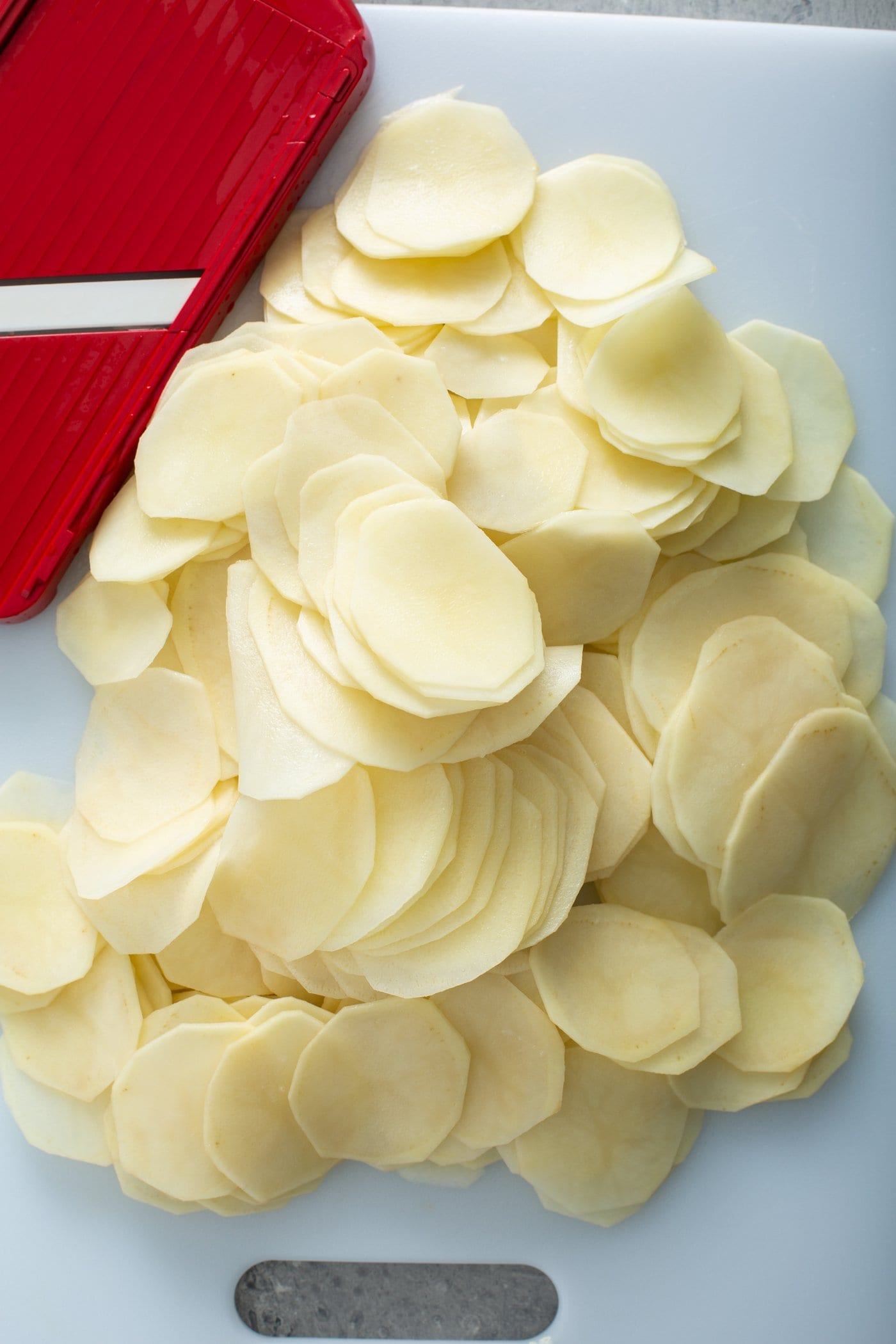 Raw, peeled, sliced potatoes with a red and white kitchen towel in the background.