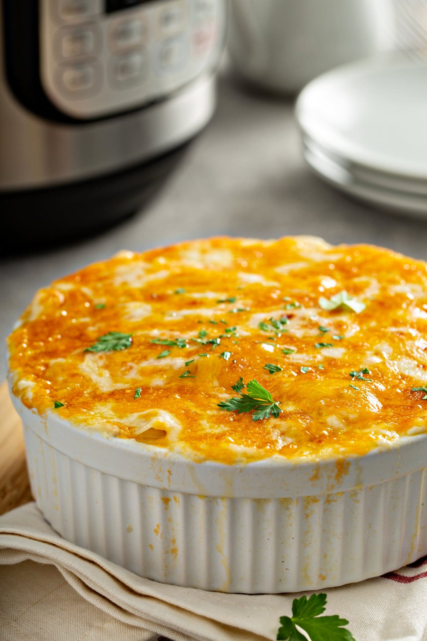 A casserole dish with cheesy potatoes topped with melted cheese and parsley leaves. There is a stack of dinner plates in the background and an instant pot.