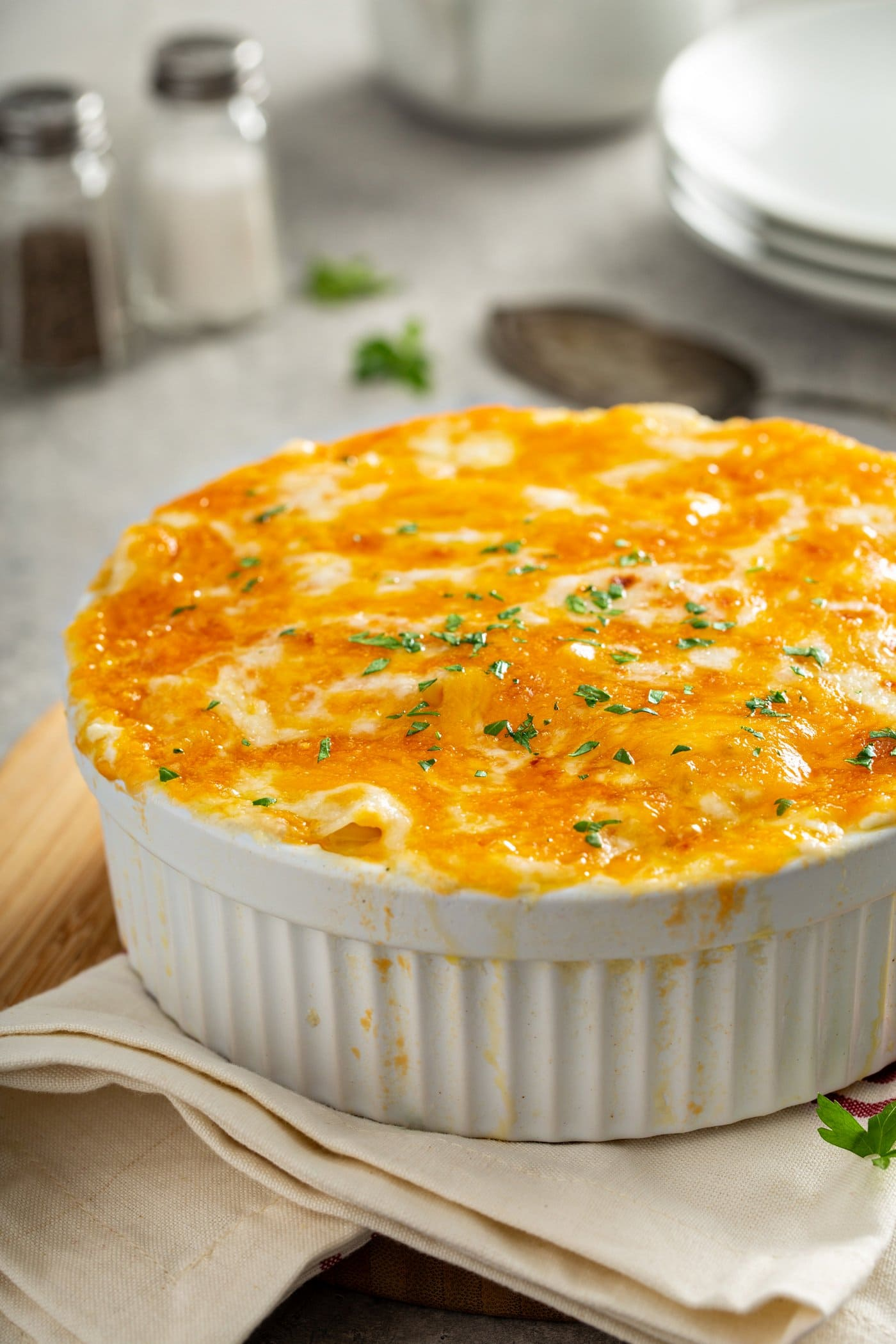 A casserole dish full of cheesy potatoes. The cheese is melted and toasted.
