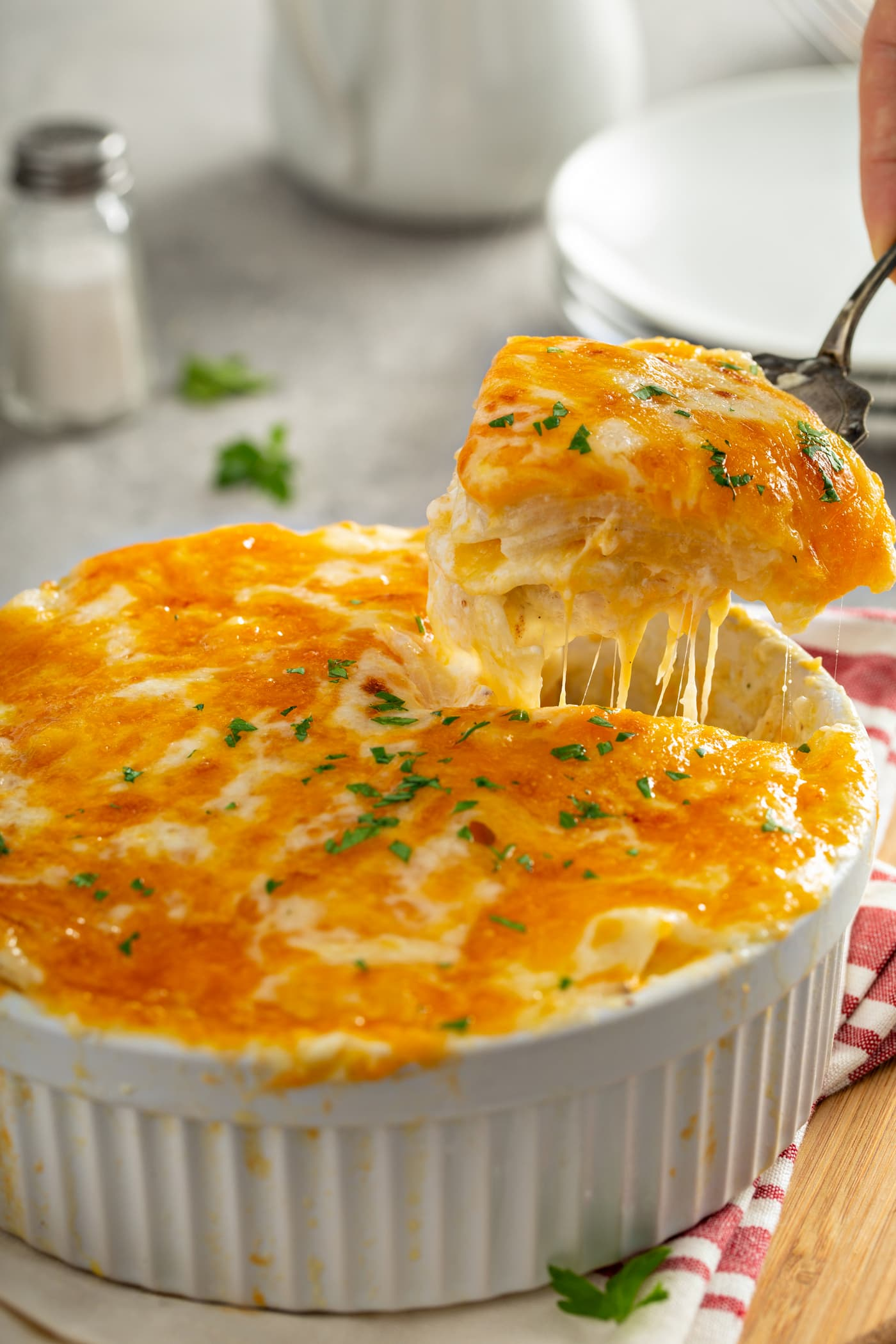 A serving of instant pot cheesy potatoes are being lifted from a white casserole dish with a serving spoon. the melted cheese is stringing out below the spoon. there is a stack of dinner plates in the background and a red and white kitchen towel beside the casserole dish.