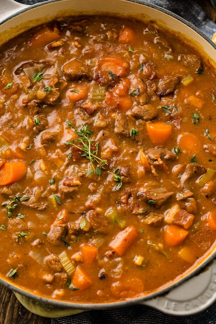 a bowl of irish beef stew with beef, carrots, celery and a wonderful gravy