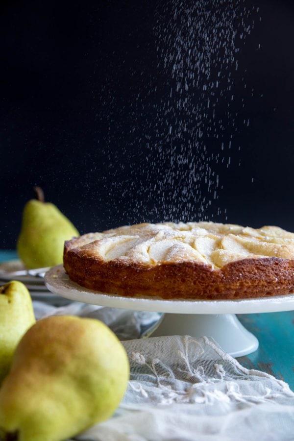 Dusting powder sugar on pear cake
