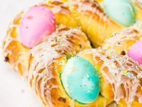A photo of Italian Easter bread with bright hard boiled eggs nestled in it, and covered in sprinkles and a sweet glaze.